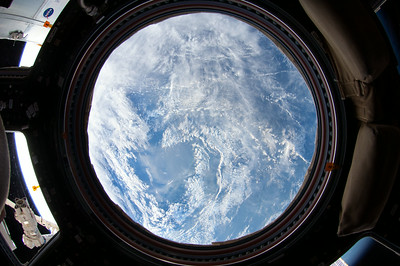 Caption by Space Station Academy student: A picture of the clouds over Manila, in the Philippines from the point of view of an astronaut hanging out in the cupola. I liked how it kind of looks like the cupola has captured the earth and it's just a mini globe in the solar system that looks so small you could put it in your pocket.