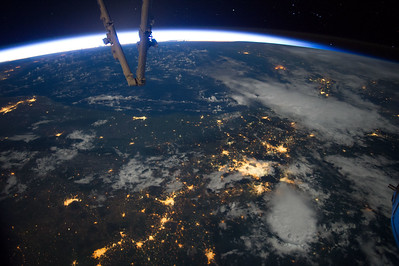 Caption by Space Station Academy student: Picture showing city lights at night. (and some ISS at the top). It's a beautiful picture. It almost looks like wildfires. I wonder if it helps research on light pollution.