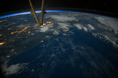 Caption by Space Station Academy student: This photo is taken at night time off the coast of Acapulco, Mexico.  There are lights representing the different cities in the area and areas of darkness where there aren't many residents.  Off to the right side of the photo (south), there are bright white lights representing a thunder and lightning storm.  This view from space of how a populated area looks is fascinating to me.  I also love how a small portion if the ISS is included in the picture.