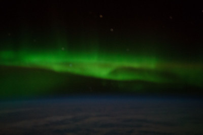 Caption by Space Station Academy student: Aurora in South Pacific in between southwestern Australia and Antarctica. There are various colors (green, black, and dark blue) in stripes across the night sky. The green pops out at you and is very fog like.