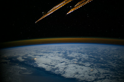 Caption by Space Station Academy student: near Tasman Sea in between Tasmania and New Zealand. This image is fascinating because we can see city lights in New Zealand, and we can also see a gold haze over the horizon---perhaps the Southern Lights?