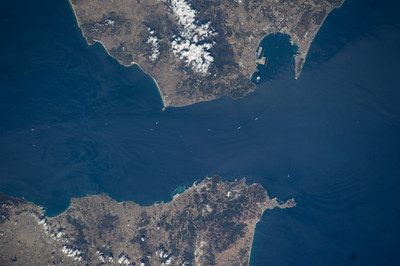 """Named indirectly for the Arabic """"Jabal Ṭāriq"""" (Tariq's Mount), this opening once saw almost 3.75M cubic km of water pass in one direction. ISS over North Africa. (ANSWER: the Strait of Gibraltar, entrance to the Mediterranean Sea)"""