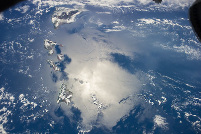 "Volcanic archipelago with a tropical climate. If measured from the sea floor the ""big"" island would be the world's tallest mountain. ISS over the Pacific Ocean. (ANSWER: Hawaiian Islands. Measured from its base on the ocean floor, Mauna Kea on Hawaii is 33,500 feet tall.)"