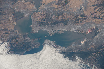 Bay/shallow estuary dominated by 3 major cities, surrounded by faults, the cable cars in one city aren't just for show, it really is that hilly! Notice the salt ponds on the right and barely visible famous bridge in the center.. ISS over eastern Pacific. (ANSWER: San Francisco Bay with San Jose, Oakland, and San Francisco, California, US)