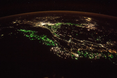 City towards upper left is capital of its country, has a metro area of 14 million, is a top tourist destination, currency is the baht. Bonus - what are the green lights? ISS over southeast Asia.
