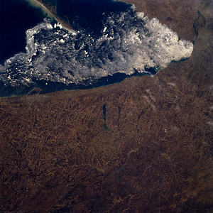 Astronaut Tom Jones: Lake Erie Ice Flow, April 15, 1994. Looking at early spring from shuttle Endeavour with my crew on STS-59, Space Radar Lab 1.   NASA: Ice flows are visible along the eastern shore of Lake Erie in this north-looking view. Lake Erie is 241 miles (388 km) long and from 30 to 57 miles (48 to 92 km) wide. Lake Erie is the fourth largest and shallowest of the five Great lakes with a maximum depth of 210 feet (64 meters), and is the only Great Lake with its lake floor above sea level. Lake Erie is partially ice bound in winter and is normally closed to ship traffic from mid-December to the end of March. As the ice begins to break up in March, predominantly westerly winds push the ice eastward toward Buffalo, New York (top right of image). The city of Erie, Pennsylvania can be seen near the left center of the image on the southern shore of Lake Erie. Presque Isle, a peninsula, is discernible protruding out into Lake Erie. This peninsula helps form Erie's superb harbor, Pennsylvania's only Great Lakes port. Portions of the dissected Allegheny Plateau can be seen covering the lower right quadrant of the image. Near the center of the image, the bluish-colored waters of Chautauqua Lake are discernible. To the south of Chautauqua Lake are sediment-laden waters of the Allegheny Reservoir.