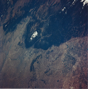 Astronaut Tom Jones:  Here's the Air Force Academy, Colorado Springs, and Denver, seen from STS-68 Endeavour on Oct. 10, 1994. My crew was over the Colorado plains east of Denver when we looked south (toward upper left) and grabbed this shot. Denver is at lower right, with both the old Stapleton International Airport (near town) and the new airport runways visible. Colorado Springs is just to the east of the white blaze of Pikes Peak at center left. The dark green comma east of the Front Range is the Black Forest, and if you look closely you can see the cadet area at USAFA, as well as Falcon Stadium in this 250mm Hasselblad shot (70mm film). The runways at Peterson Field (AFB) are easily visible east of C. Springs. The Arkansas River runs west to east from Canon City to Pueblo, to the left of Pikes Peak. I learned to fly in 1974 at the Academy airfield, barely visible near Falcon Stadium.