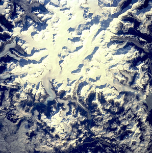 """Astronaut Tom Jones: On Oct. 1, '94, my crew was conducting our 2nd day of orbital operations on Space Radar Lab 2. Our orbit, inclined 57 deg. to the equator, brought us over some beautiful territory seldom seen from space. Here we are over a brilliant snow field and glaciers of the Coastal Mountains on the British Columbia--Alaska border. You'd need sunglasses on to look down at this scene. North is at top. Some place names here include Shakes Lake, Devil's Thumb, and LeConte Bay. If you Google """"Mount Burkett"""" in Alaska, you'll find this scene. Write me if you've been on the ground here!  NASA: The margins of the large ice field (white area) in the center of the picture show many valley or alpine glaciers descending from the higher elevations of this section of the Coast Mountains (Canadian-U.S. Border). The ice field straddles the Canadian-U.S. border at 57 degrees north latitude. Mt. Burkett (9730 feet - 2966 meters) and Kate's Needle (10023 feet - 3055 meters) are just two of the many ice covered peaks, known as horns, that are observed in this image. Clouds obscure the Stikine River Valley."""