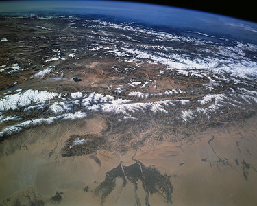 Astronaut Tom Jones: When we reached orbit on Sept. 30, '94, the Taklamakan was a major landmark and science target for Space Radar Lab 2. Our radar targets were the alluvial fans and dune fields along the southern margin of the Taklamakan, where the Silk Road oases hosted caravans and travelers on an ancient trade route. Note the alluvial fans and vegetation in foreground, fed by streams from the Altyn-Tagh mountains bordering the desert on the south. Our radar images found traces of Silk Road irrigation channels and sand-covered villages.  NASA: This south-looking view shows most of the west end of snow-dusted ranges on the Tibetan Plateau. A major fault line separates the plateau from the low-lying Takla Makan Desert (foreground). The darker areas along two rivers (foreground) make up one of the largest agricultural regions in the Takla Makan Desert. The hazy atmosphere over India (top) contrasts with the thinner, clear air over the plateau. The Vale of Kashmir in northern India is the prominent valley within the first wall of the Himalayan Mountains.