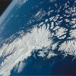 Astronaut Tom Jones: On our STS-68 Endeavour flight in 1994, our crew took in this view of the St. Elias Mountains, the Fairweather Ranger, and Malaspina Glacier (lower left). Malaspina in southeastern Alaska is considered the classic example of a piedmont glacier. Piedmont glaciers occur where valley glaciers exit a mountain range onto broad lowlands, are no longer laterally confined, and spread to become wide lobes. Malaspina Glacier is actually a compound glacier, formed by the merger of several valley glaciers, the most prominent of which seen here are Agassiz Glacier (left) and Seward Glacier (right). In total, Malaspina Glacier is up to 65 kilometers (40 miles) wide and extends up to 45 kilometers (28 miles) from the mountain front nearly to the sea.  Just to the upper left of Malaspina is the craggy summit of Mt. St. Elias, at 18,009 ft above sea level. In the far right on the Pacific coast is Fairweather Mountain, just northwest of Glacier Bay National Park (just off the photo to the right). We always searched the Alaska coast for Malaspina, as it's such a landmark and favorite photo target. Later, in summer 2000, I was able to visit this section of the coast on a cruise with my family.
