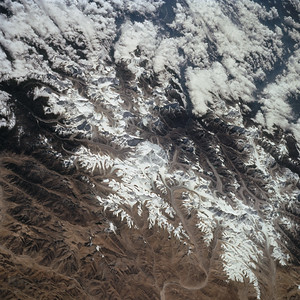 """Astronaut Tom Jones: This must be one of the most astounding views of Earth for space crews: the roof of the world, including the Tibetan plateau and the upthrust peaks of the Himalaya. I learned before my first flight how to find Everest from space: follow the left branch of the V-shaped valley at lower right center, and it leads one straight to Everest. I once woke up at """"3 am"""" ship's time, using my watch alarm, to make sure I spotted Everest after leaving the Space Station--the view is that spectacular.  NASA: This south-looking, summer-time view of Mt. Everest (center) - with strong sense of three dimension because of reduced amount of snow - and neighboring peaks of the Himalayas. Clouds cover lower slopes in India."""