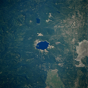 Astronaut Tom Jones: This area of the U.S. got repeated attention from our SRL-2 crew, with multiple science sites along the Cascade Range of volcanoes. During training flights with an airborne radar system, Linda Godwin and I flew over Mt. St. Helens and Mt. Rainier. The 1980 St. Helens eruption killed more than 60 people and devastated thousands of square miles around the volcano. Volcano monitoring from space is a key ability of imaging radar, especially for those active volcanoes  in remote or poorly studied areas. Gorgeous Crater Lake is on my list for a visit within the next three years.   NASA: Crater Lake (center of photograph), the second deepest lake in North America at 1932 feet (590 meters), is displayed in this spectacular, low-oblique, north-looking photograph. Only Canada's Great Slave Lake is deeper-by 83 feet (25 meters). Crater Lake is 6 miles (10 kilometers) wide and covers 20 square miles (50 square kilometers). The lake lies in a huge caldera that was created more than 7000 years ago when the top of Mount Mazama Volcano was blown off by a violent eruption. Mount Mazama began to form more than 1 million years ago. The volcano reached an estimated altitude of nearly 12 000 feet (3600 meters) through a series of eruptions. With most of its magma and other materials exhausted following the violent eruption 7000 years ago, the foundation of the mountain was weakened. Geologists estimate that Mount Mazama collapsed around 4600 B.C., and the caldera was created. Having no inlet or outlet, the lake formed as a result of runoff from rain and snow. Cliffs surrounding the present lake vary from 500 to 2000 feet (150 to 600 meters) above the lake. Wizard Island-a cinder cone about 776 feet (230 meters) high, which formed by volcanic activity after the collapse of Mount Mazama-is near the western shore of the lake. Crater Lake, originally named Deep Blue Lake because of its sapphire hue indicating both extreme depth and extreme purity, was designated a Natio