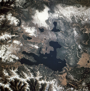 Astronaut Tom Jones: I've been to Yellowstone twice. It's a scenic wonderland, with a steaming river, clockwork geysers, bubbling mud pots, bears, deep blue lake, waterfront lodges, rainbow-hued hot springs, and a forest regrown from a wildfire. Zeroing in on it from orbit just made me more anxious to get there again. What a country!  NASA: Photographed through the Space Shuttle Endeavour's flight windows, this 70mm frame centers on Yellowstone Lake in the Yellowstone National Park. North will be at the top if picture is oriented with series of sun glinted creeks and river branches at top center. The lake, at 2,320 meters (7,732 feet) above sea level, is the largest high altitude lake in North America. East of the park part of the Absaroka Range can be traced by following its north to south line of snow capped peaks. Jackson Lake is southeast of Yellowstone Park, and the connected Snake River can be seen in the lower left corner. Yellowstone, established in 1872 is the world's oldest national park. It covers an area of 9,000 kilometers (3,500 square miles), lying mainly on a broad plateau of the Rocky Mountains on the Continental Divide. It's average altitude is 2,440 meters (8,000 feet) above sea level. The plateau is surrounded by mountains exceeding 3,600 meters (12,000 feet) in height. Most of the plateau was formed from once-molten lava flows, the last of which is said to have occurred 100,000 years ago. Early volcanic activity is still evident in the region by nearly 10,000 hot springs, 200 geysers and numerous vents found throughout the park.