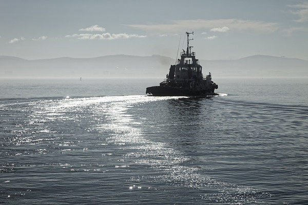 Fishing vessel setting off in Table Bay, South Africa