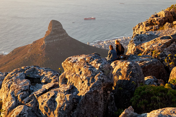 View over Lion's Head and Sea point enjoyed by two visitors on Table Mountain, Cape Town