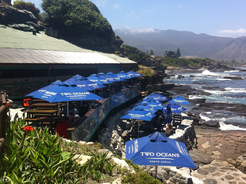 The restaurant tables are right on the shore line with the cave itself behind