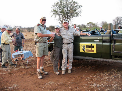 "Our Mala Mala Main Camp Guide, Graham,  handing Susan her Sundowner drink on Our National Geographic Expeditions ""South Africa by Private Air"" expedition. NGE guide Dr. Bill Branch on left, facing camera with binocs around his neck."