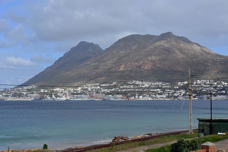 Simon's Town, 13 September 2018.  Looking east.  Simon's Town has been a naval base since the 1700s.  It was used by the Royal Navy until 1957 when it was handed over to the South African Navy, who still use it.  In the foreground is the electrified single track railway from Cape Town.
