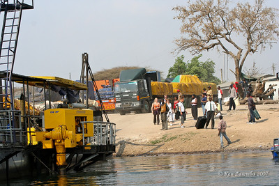 People in Zambia waiting for small boats to transport them across the Zambezi river while big trucks wait for the large ferry (It only holds ONE large truck at a time!) Autos get priority.