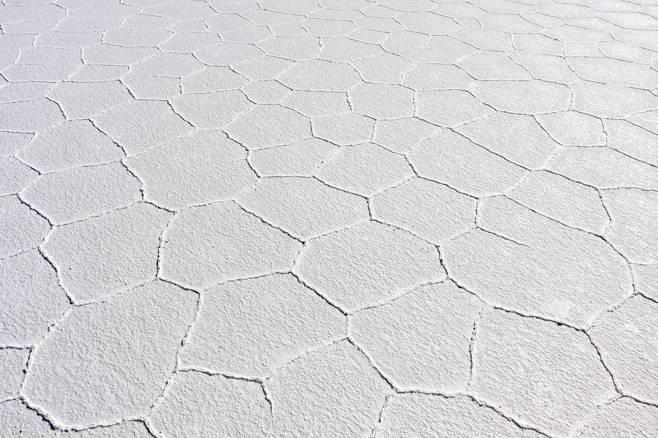 Subterranean water rises up through solidified layers of salt and evaporate in the intense sun, leaving evocative 6(ish)-sided hexagonal patterns behind.<br /> <br /> Location: Solar de Uyuni, Bolivia<br /> <br /> Lens used: Canon 17-55mm f2.8 IS