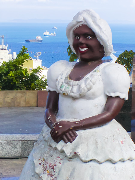 This is a monument to a woman in traditional costume in Salvador, Bahia, Brazil. The statue commemorates a story from the Afro-Brazilian slave past but I cannot find any further mention of the story nor the woman's name.
