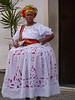 Costumed Woman in traditional dress posing for tourist oney in Salvador, Bahia, Brazil