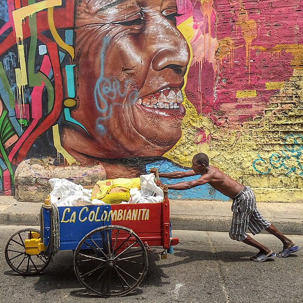 """Colombianita, the streets of Cartagena in art, a man wheels concrete in a push cart. This is Colombia. Our latest piece -- """"Colombia First Impressions"""" is up in the blog (link in profile). via Instagram http://ift.tt/1Igplc1"""