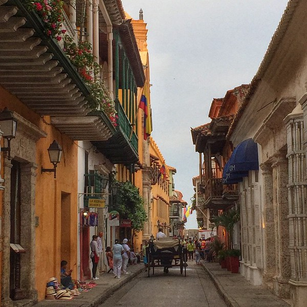 A first look down the lane, Cartagena old town. Steamy, colorful, Caribbean. Founded in 1533 by the Spanish, the town first served as a store for gold, silver and other riches taken from its Latin American colonies before it was all loaded on pirate-dodging ships for home. Cartagena retains much of its colonial look and feel. Unsurprisingly, it's a popular UNESCO site and flush with salsa bars, horse-drawn carriages, colorful balconies, and fruit carts. There's even a creepy mime who follows everyone around under the old town clock tower. via Instagram http://ift.tt/1LUoKjp