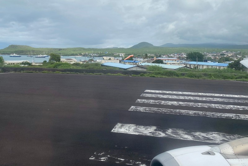 Taxiing at the end of the SCY runway for takeoff. Our dive boat, Galapapos Master, is visible, anchored in the harbor, left of the tree (leftside).