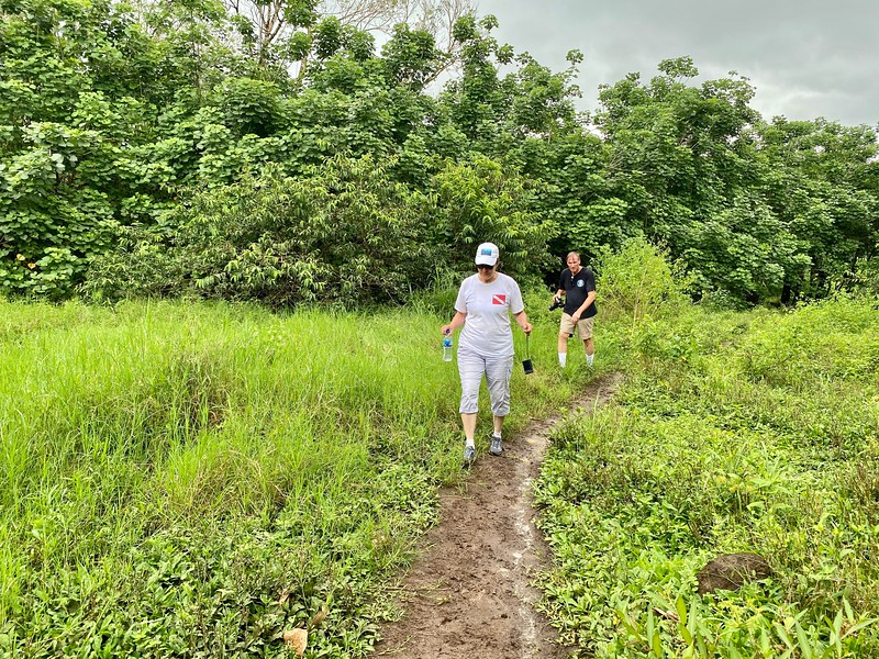 Merry & Phil navigate muddy path, in search of giant tortoises