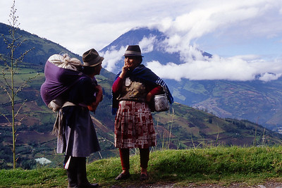 Two local women visit with Tungurahua volcano in background