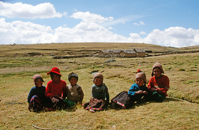 "Highlands children sitting on ""Puna"" (open, arid grasslands, Mount Ausangate circuit"
