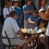 A sidewalk chess match with a crowd