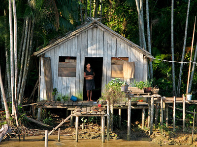 Woman and house along the Amazon River - Brazil