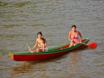 Two women paddle a canoe on the Amazon River - Brazil