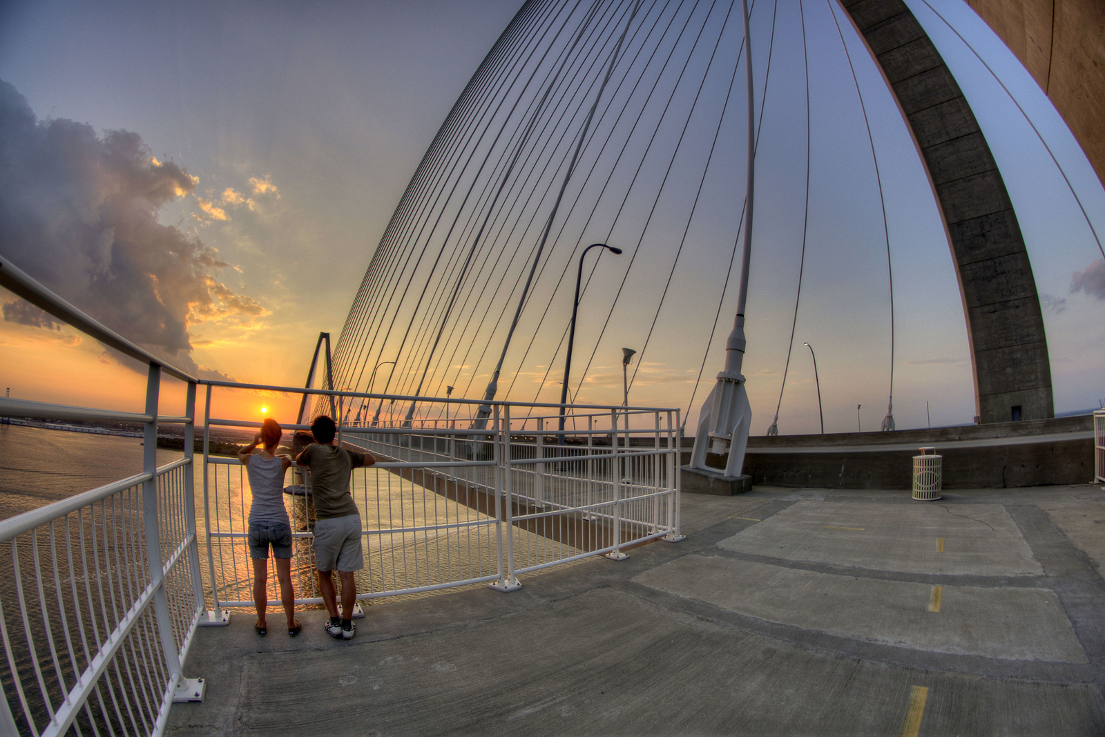 A couple watches a warm sunset from Wonders' Way on the Arthur Ravenel, Jr. Bridge in Charleston, SC on Sunday, September 8, 2013. Copyright 2013 Jason Barnette