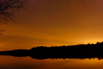 Hours after sunset, stars begin to streak across the firey sky during this long exposure view over Juniper Lake in Cheraw State Park, a 7,300-acre park featuring camping, hiking, golf, and a beautiful lake, in Cheraw, South Carolina on Friday, March 4, 2011. Photo Copyright 2011 Jason Barnette