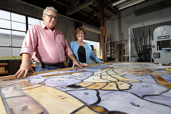 Artists Ed and Barbara Streeter pose for a photo in front of a stained glass window under construction at Conway Glass in Conway, SC on Monday, September 1, 2014. Copyright 2014 Jason Barnette