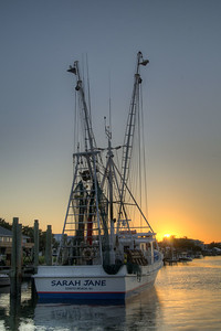 The sun sets along the water beyond a fishing boat in Edisto Beach, SC on Friday, August 29, 2014. Copyright 2014 Jason Barnette