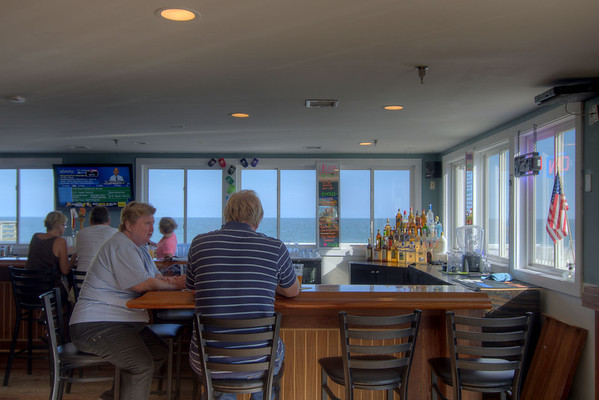 People enjoy drinks and food inside the oceanfront Fins Restaurant and Bar, a locally owned restaurant, in Edisto Beach, SC on Friday, August 29, 2014. Copyright 2014 Jason Barnette