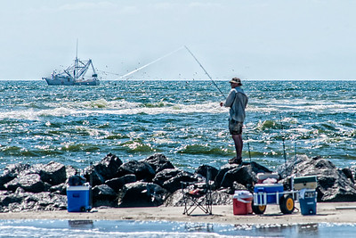 A man fishes along the beach jetty as a boat fishes out at sea at Folly Beach, SC on Friday, May 27, 2016. Copyright 2016 Jason Barnette