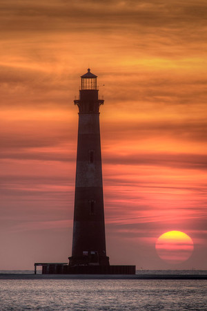 The sun rises above the horizon near the Morris Island Lighthouse in Folly Beach, SC on Tuesday, June 14, 2016. Copyright 2016 Jason Barnette