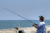 A man fishes on the Edwin S. Taylor Fishing Pier in Folly Beach, SC on Sunday, September 8, 2013. Copyright 2013 Jason Barnette