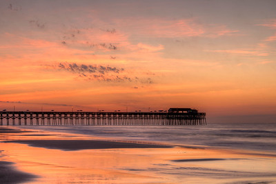 A warm dawn sky over the fishing pier in Garden City Beach, SC on Tuesday, June 21, 2016. Copyright 2016 Jason Barnette
