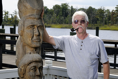 Sculpter Roy Smith poses beside a towering wooden totem pole he created on the Marshwalk in Georgetown, SC on Tuesday, September 2, 2014. Copyright 2014 Jason Barnette