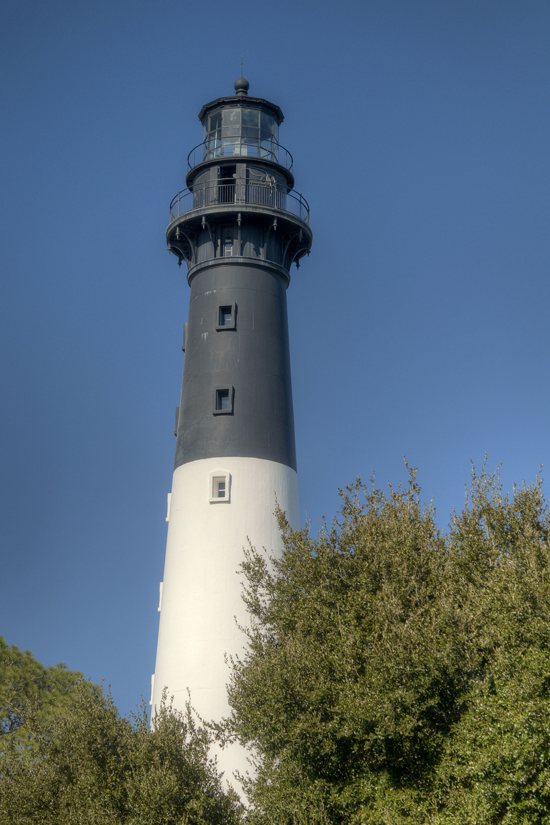 The Hunting Island Lighthouse at Hunting Island State Park in Hunting Island, SC on Friday, February 20, 2015. Copyright 2015 Jason Barnette Completed in 1875, the 133' lighthouse is one of only two segmented cast iron lighthouses in the country. The segments are made of cast iron, lined with brick, and intended to be moved if necessary. In 1888 the lighthouse and keeper's house was moved a mile inland to its current location. Today visitors can climb the 167 steps to the circular observation platform 110' high for spectacular views of the local coastal landscapes.