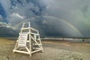 People on the beach admire the full rainbow stretching across a lifeguard chair at Huntington Beach State Park in Murrells Inlet, SC on Wednesday, July 6, 2016. Copyright 2016 Jason Barnette