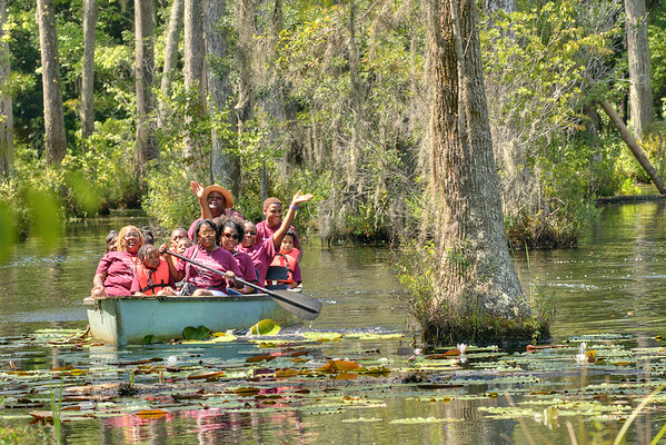 A group of people wave and smile during a boat tour of the marshes at Cypress Gardens in Moncks Corner, SC on Saturday, September 7, 2013. Copyright 2013 Jason Barnette