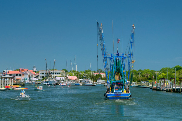 The towering fishing boat moves upstream, surrounded by other boaters and paddleboarders at the Shem Creek Boardwalk in Mount Pleasant, SC on Friday, May 27, 2016. Copyright 2016 Jason Barnette