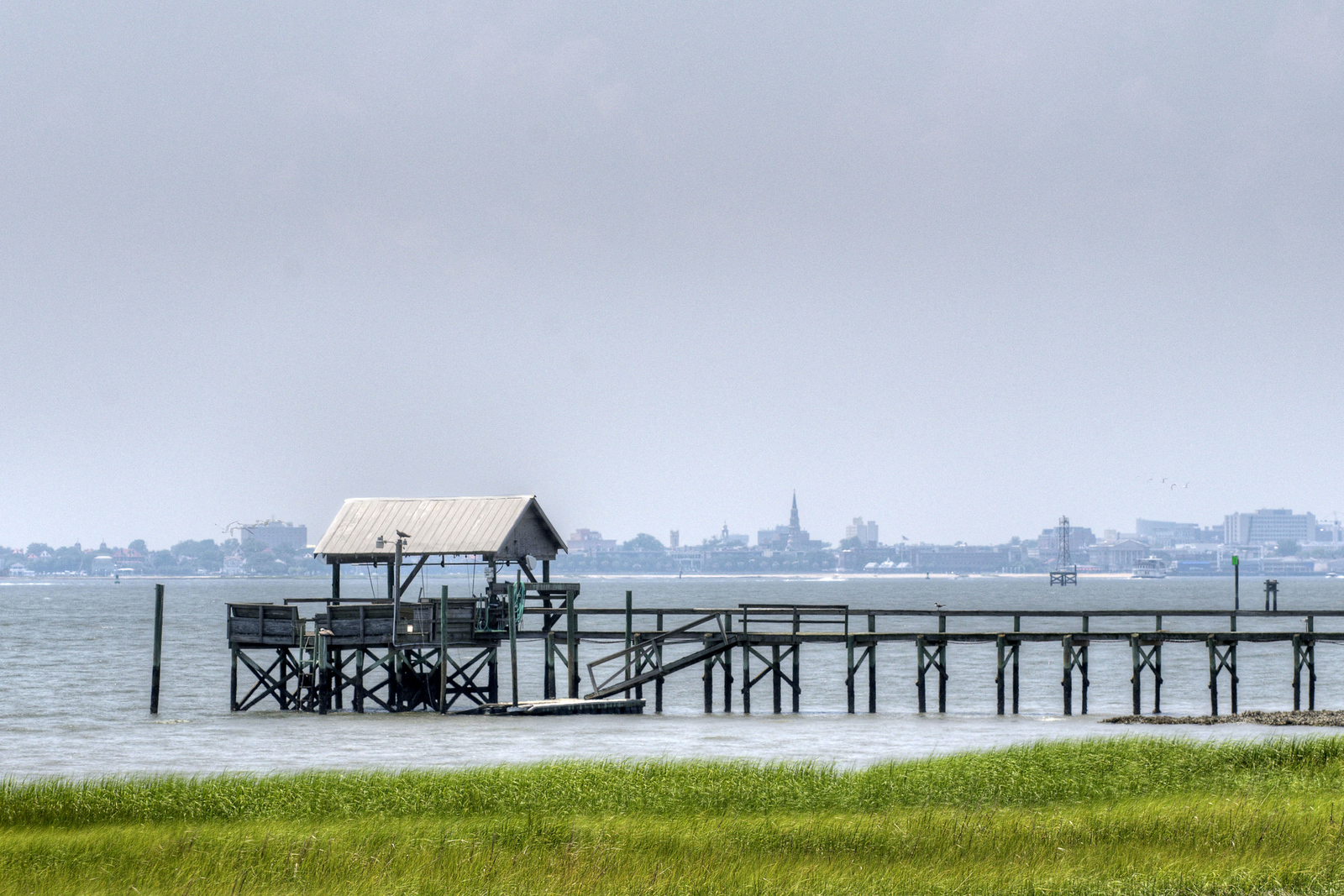 A view of a boat dock with downtown Charleston in the distance at Pitt Street Park in Mt. Pleasant, SC on Wednesday, July 9, 2014. Copyright 2014 Jason Barnette Pitt Street Park is located on the site of the former Pitt Street Bridge that once connected Mt. Pleasant with Sullivan's Island. When the nearby Ben Sawyer Bridge was completed, the Pitt Street Bridge was abandoned. Today, the bridge only stretches half the distance it once did, but serves as a pedestrian greenway with a wooden boardwalk along the old concrete pillars, providing a place for walkers, joggers, bikers, and fishermen to enjoy the space.